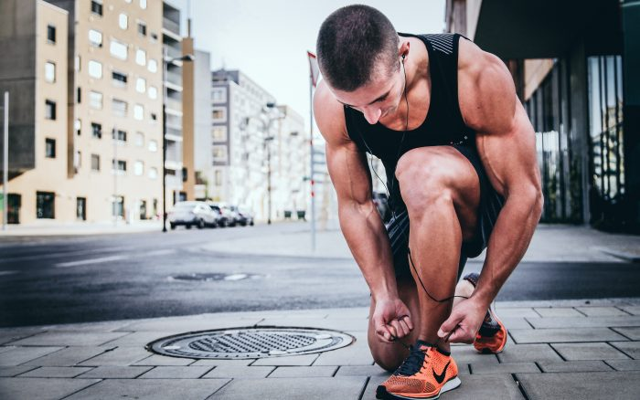 Muscular man tying running shoes
