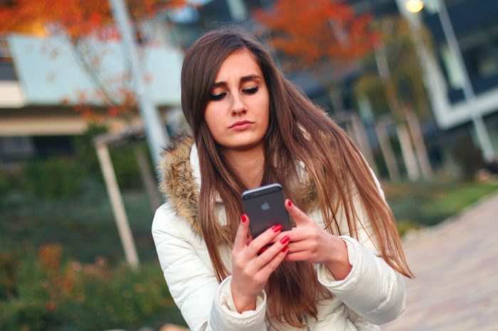 Sad Girl Looking at Cell Phone