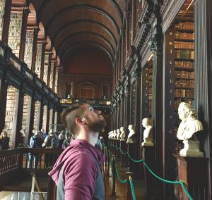 Man looking up at tall bookshelf in ornate library with stone statues.