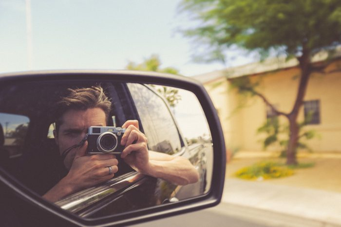 Man in car taking picture of self in side mirror.